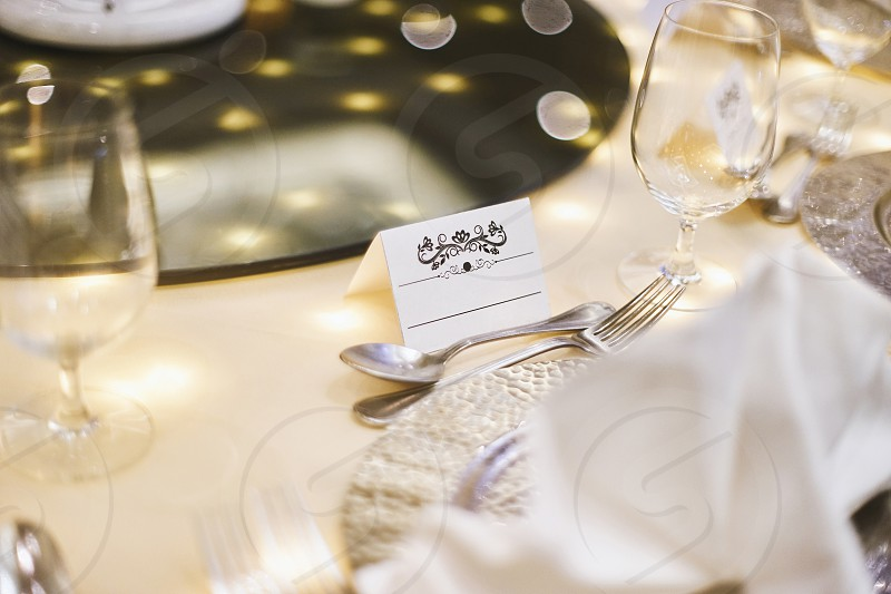 Mock up for white label with ornament art for name tag on the dinner table with bokeh and blurry foreground and background photo