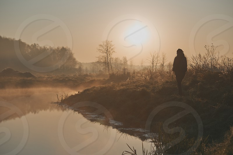 Woman walking through a meadow by a pond in the foggy morning. Sun rising above field and pond flooded with fog in the morning. Real people authentic situations photo