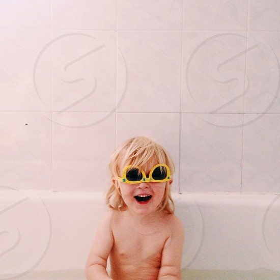 a little girl wearing a yellow sunglasses sitting on a white bath tub photo