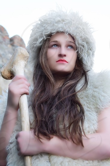 woman in white fur hoodie holding white wooden cane during daytime photo