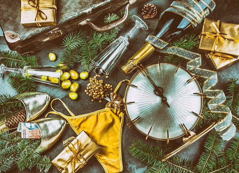 LATIN AMERICAN AND SPANISH NEW YEAR TRADITIONS. empty suitcase lentil spoon yellow interior clothes gold ring in champagne 12 grapes money in shoe - ARGENTINE MONEY. Christmas background. photo