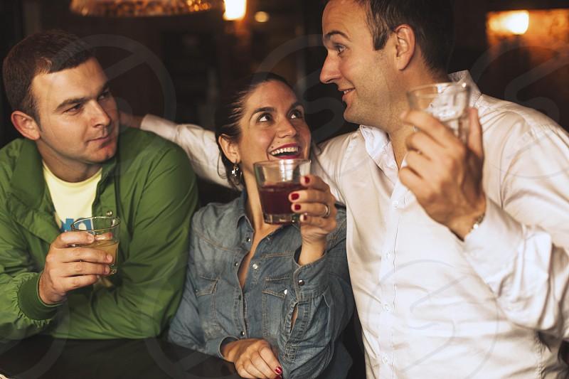 Three friends holding drinks and having fun. photo