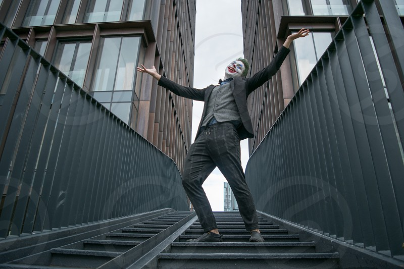 Male comics character cosplayer standing on stairs spreading his arms happily smiling photo