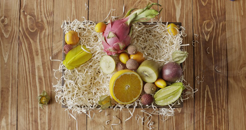 Box with assortment of freshly picked natural exotic fruits on a wooden background. Girl's hand puts ananas passion fruit mango on a wood shaving. Motion 4K UHD video 3840 2160p. photo