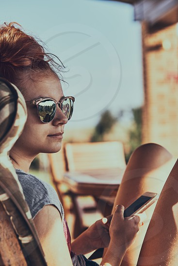 Young woman talking on a  mobile phone sitting in a chair outdoors on patio wearing a sunglasses. Real people authentic situations photo