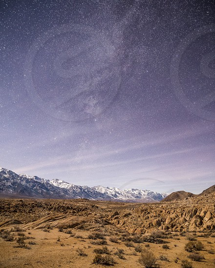 snow covered mountain under starry sky across brown desert photo