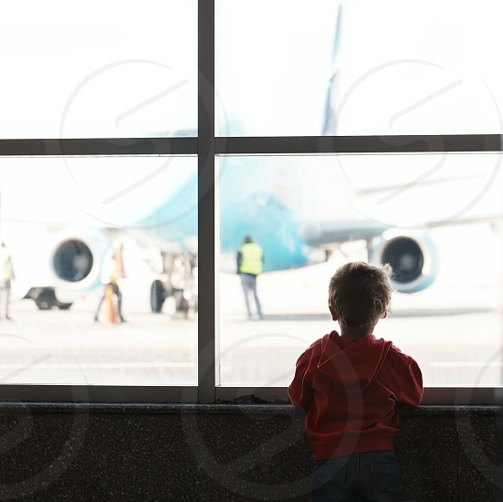 Boy looks at the plane at the airport silhouette shot from back photo