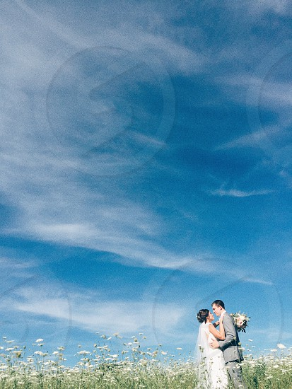bride and groom prenup under blue and white sky photo