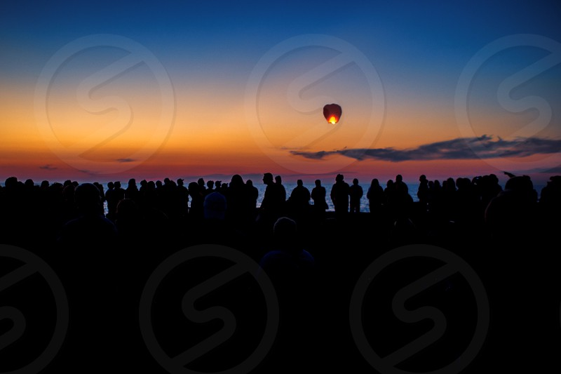 Paper Lantern on Crowded Beach at Sunset photo