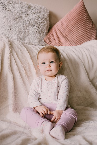 Adorable baby girl sitting on a white couch.  Relaxing time at home.  Toddler.  photo