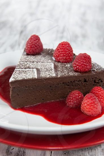 Chocolate Torte flour-less chocolate flour-less torte raspberries rustic white background raspberry coulis red brown dessert creamy ganache photo