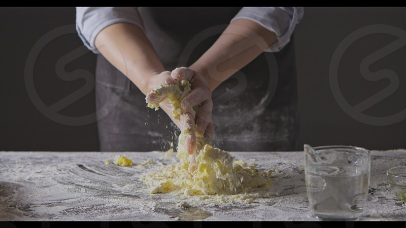 Professional chief is kneading homemade dough on a kitchen table on a black background. Slow motion Full HD video 240fps 1080p. Process preparing of homemade pasta. photo