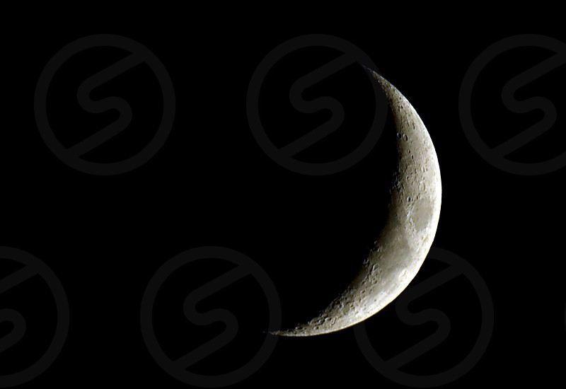 A crescent moon in the night sky photo