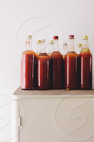 Bottles of fresh homemade strawberry juice on the cabinet photo