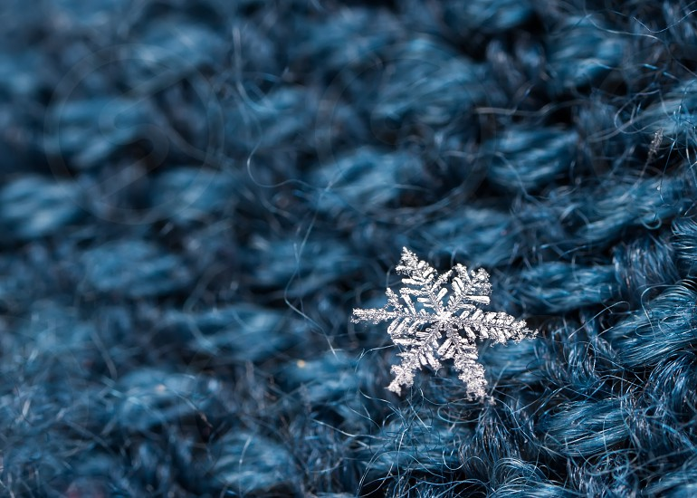 Extreme macro of snowflake crystals on hairy glove photo