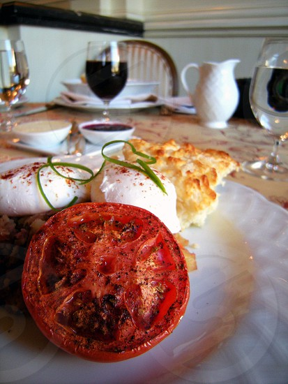 Breakfast broiled tomato on plate with poached eggs biscuit grape juice in wine glasses photo