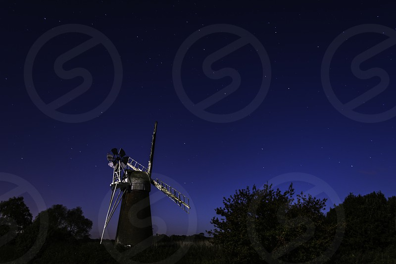 The windmill at Howe Hill under the stars at night lit only by moonlight photo