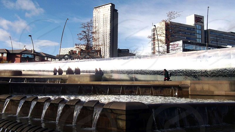 10/11/13 SHEFFIELD. Sheaf Square the water feature. A view with people and looking towards the city centre tower blocks. photo