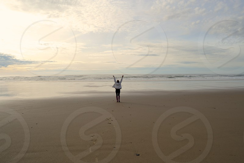 person in white jacket standing on top of brown sand in front of body of water photo