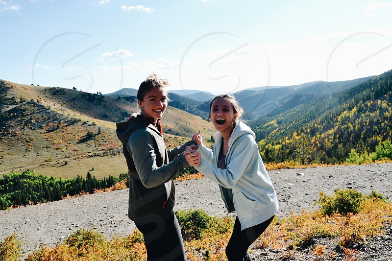 two girl in hoodie laughing in front of camera while holding there hands photo