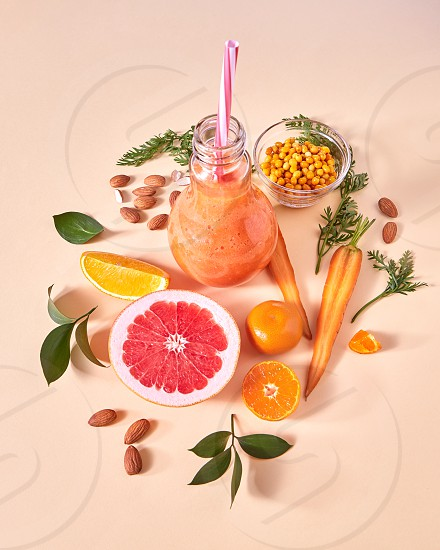 Natural freshly picked yellow vegetables and fruits berries almond nuts for preparing healthy vegetarian smoothie in a glass jar on a paper. Flat lay. photo