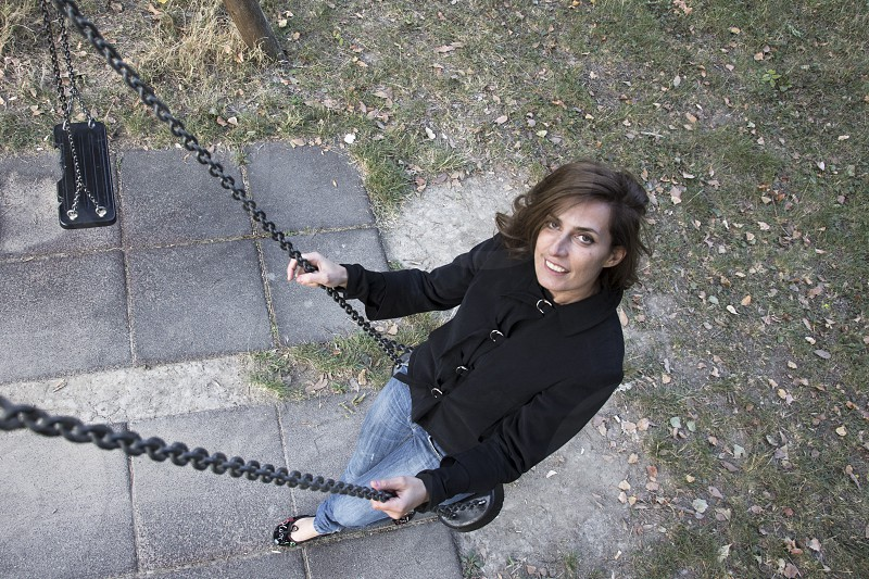 woman in blue stonewashed jeans sitting on swing photo
