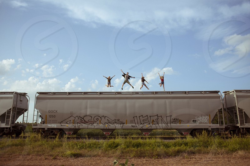 group of people jumpink on top of train photo