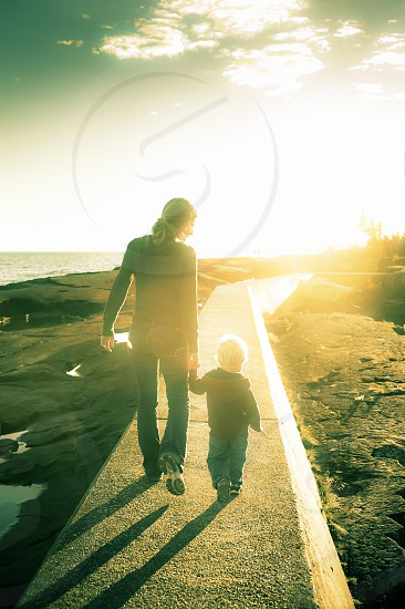 love mother son family youth child learning walking shadows sunset sun flare pier sweatshirt red green blue sky rocks lake ocean shoes blonde boy kid girl male female hands holding ponytail cute photo