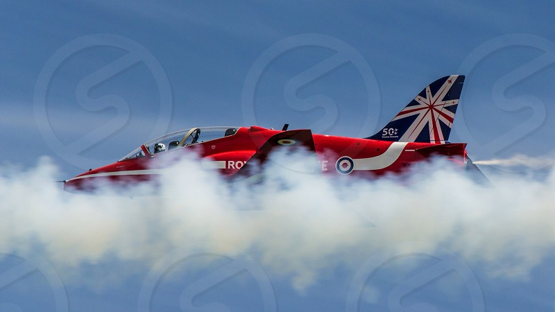 British Red Arrows jet in smoke from jet ahead. taken from the ground with 400mm lens. photo