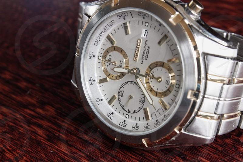 silver link bracelet white round chronograph seiko watch reading 11:38 photo