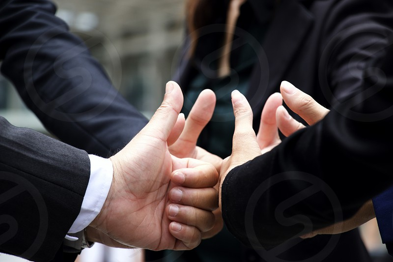 Hands of teamwork giving sign thumbs up photo