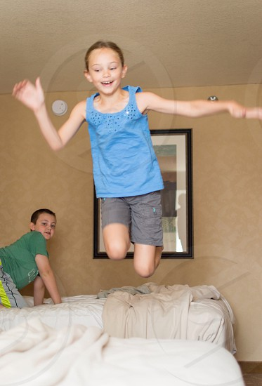 girl in blue tank top jumping over bed photo