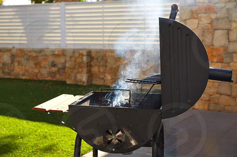 Barbecue with smoke side view in a masonry turf backyard photo