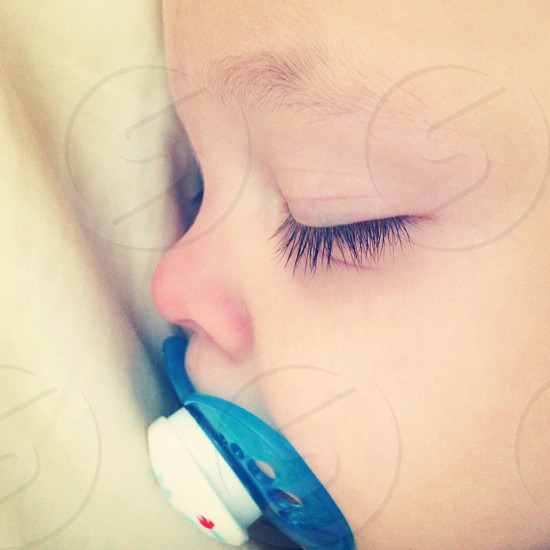 baby with blue and white silicone pacifier photo