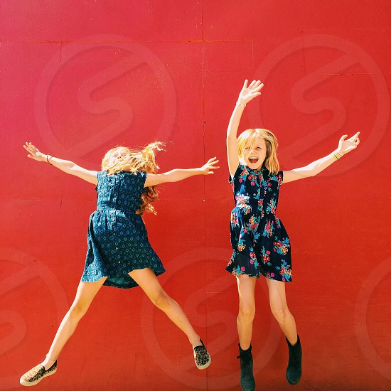 two girls in floral tank dresses jumping photo