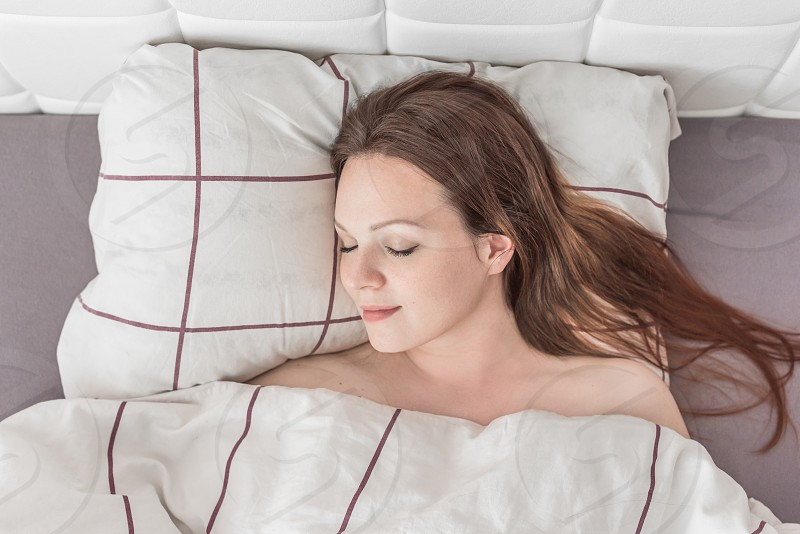 Young woman sleeping relaxed and smiling in her bed. photo