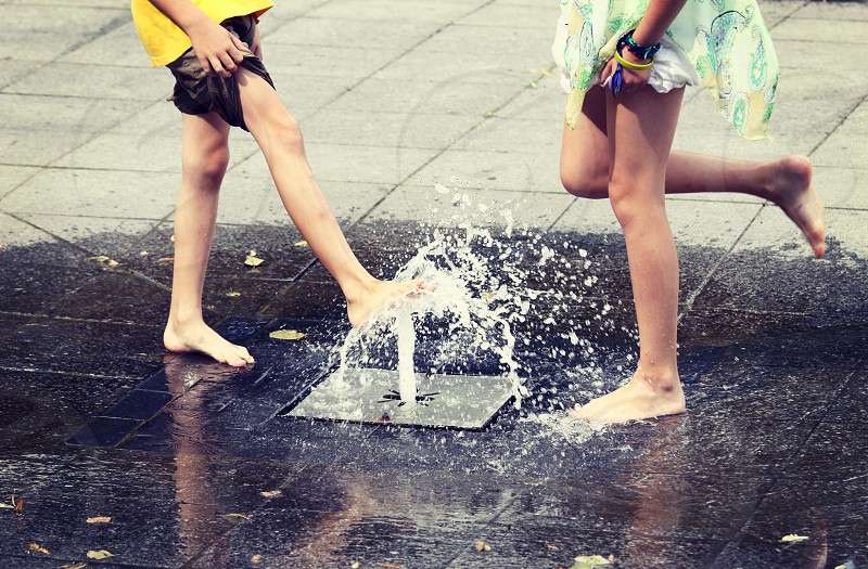 legs children playful fountain summer summertime water splash wet street outdoors city bare foot photo