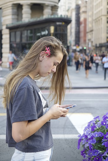 Pretty young woman checking email on iPhone in the City    photo