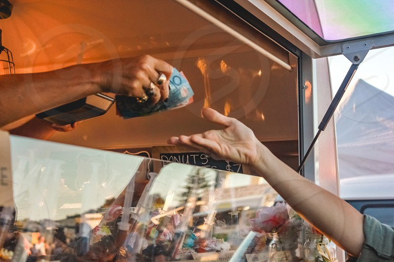 paying for treats bought from a food truck at a music festival human hand holding money purchase finance  photo