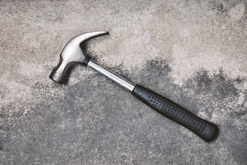 Home working tools for repairing Old steel hammer with oxides on dusty cement background with copy space photo