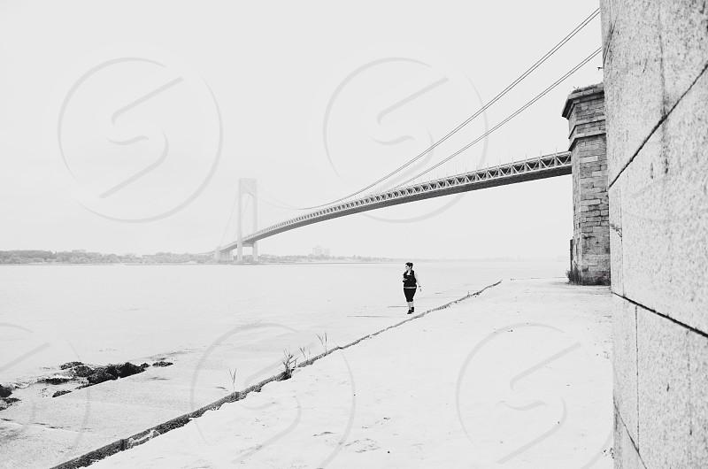 woman in black on bridge near water photo