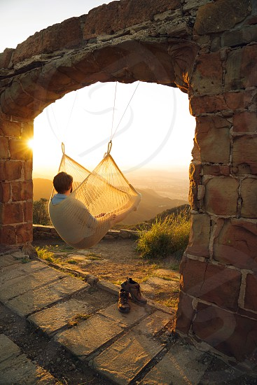 man in  grey in white net hammock hanging under adobe wall arc looking at orange setting sun in horizon photo
