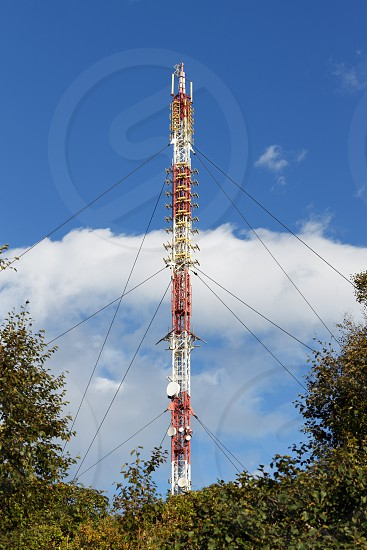Communications tower with antennas wireless communication channels such a mobile phone tower cellphone tower phone pole surrounded by trees in forest on background blue sky with white clouds. photo