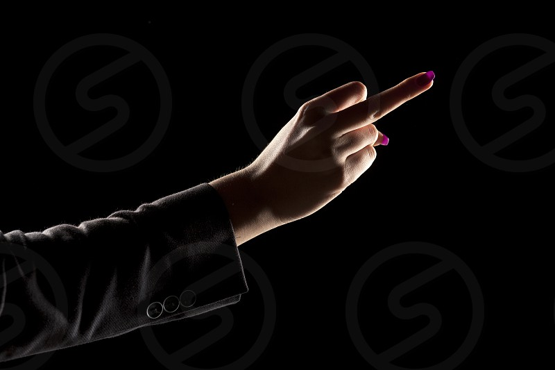 female's hand on a dark background showing middle finger photo