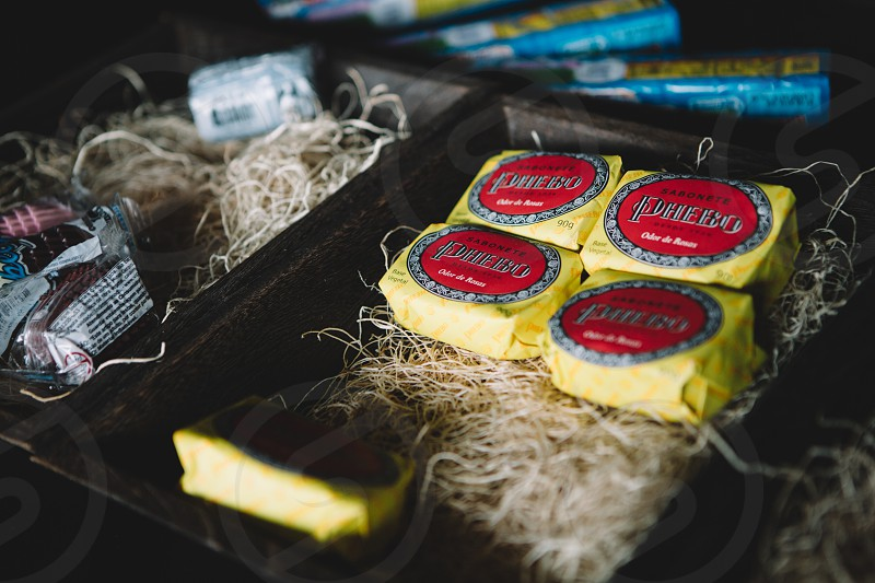 yellow and red square labeled mini pack on brown wood strings inside black wooden box photo