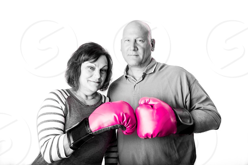 Husband and wife wearing pink boxing gloves in a studio setting. Breast cancer awareness. Survivor. photo