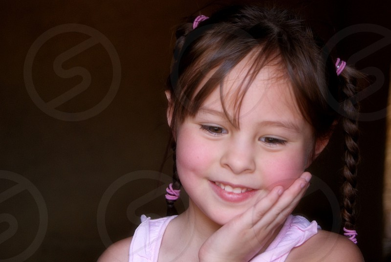 Little girl with pig tails on pink photo