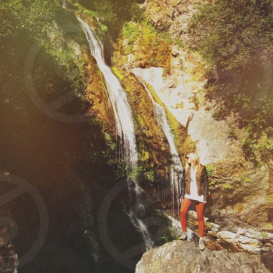 woman standing near waterfalls photography photo