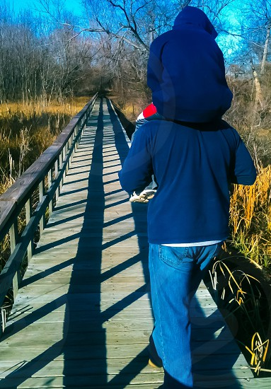 Uncle and nephew on a winter walk over a bridge of shadows surrounded by nature. photo