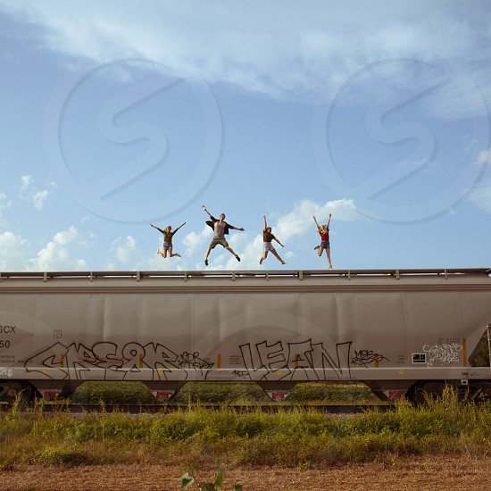 4 people jumping on top of cargo train photo
